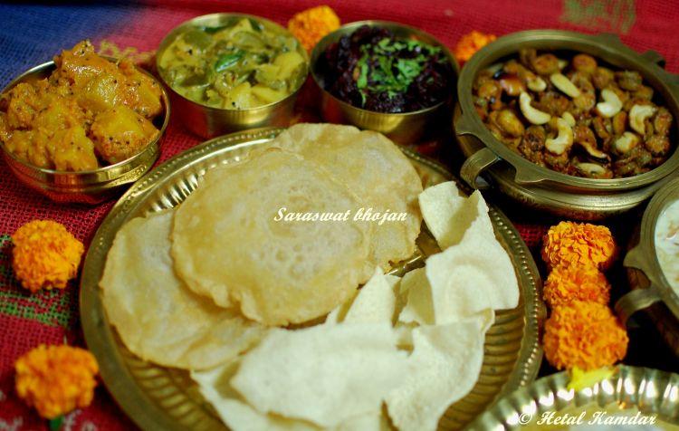 close up view of Saraswat recipes like Beetroot sukke, Pooris Appalam Madras cucumber relish, Savoury buttermilk pancakes, Coconut rice,Pumpkin phodyo, pappadam, Kairas , served on a brass platter