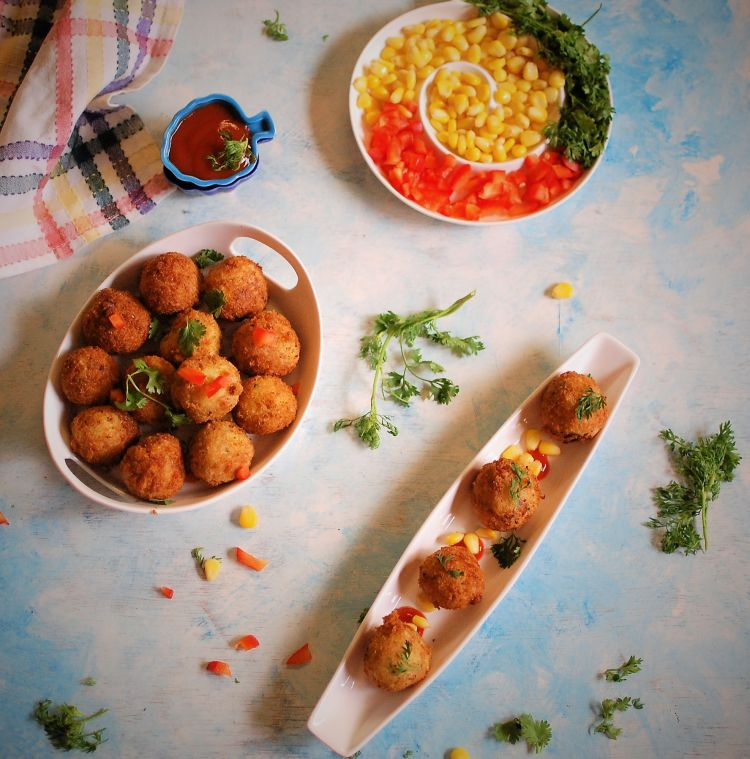flat layout of crispy and crunchy cheese corn balls recipe served with boiled sweet corns and garnished with coriander leaves