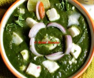 Close-up view of palak paneer garnished with onion slices and a slice of lemon