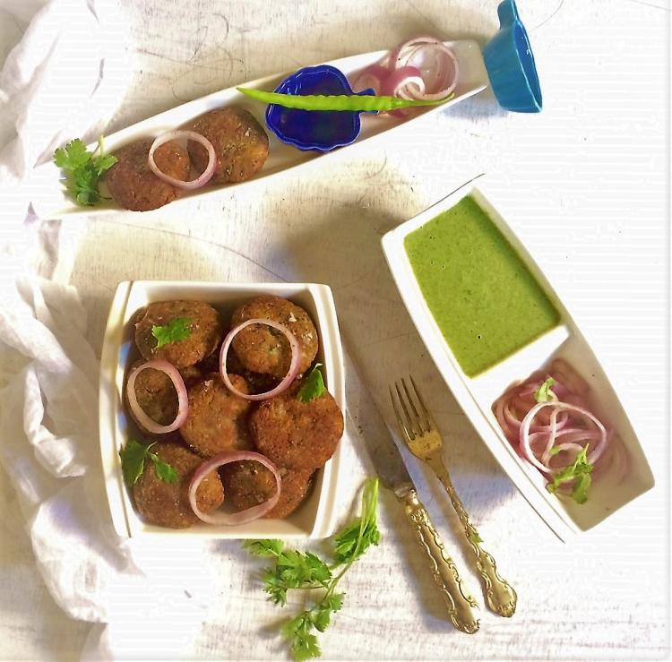 shammi kababs spread on a white board and served with mint chutney and onion slices |vegetarian shami kebabs mughlai | veg shammi kababs recipe