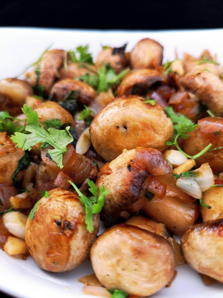 close up photo of garlic mushroom garnished with coriander leaves, how to make garlic mushroom