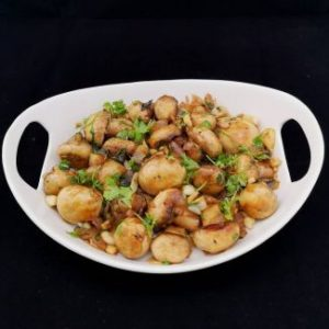 close up view of garlic mushrooms garnished with finely chopped coriander leaves, served on a white platter