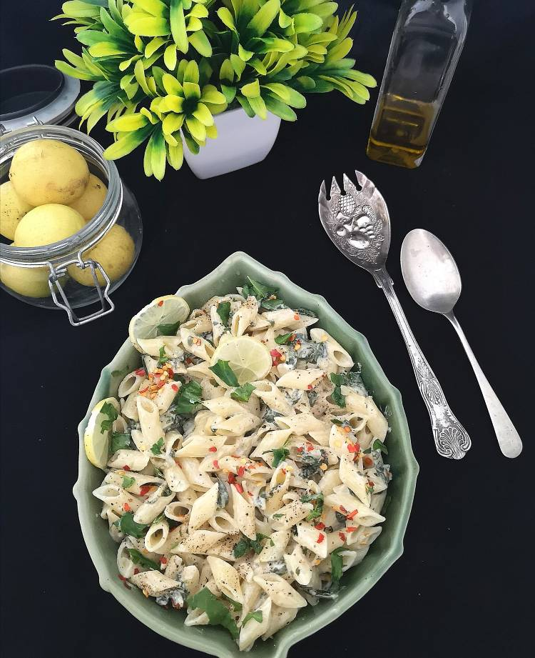 overhead photo of lemon pasta topped with chili flakes, lmeon slices, and served with silvery cutlery and lemons in a glass jar