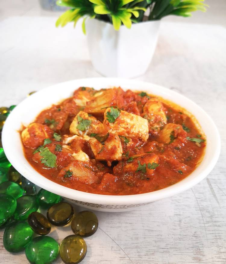 paneer aloo recipe, aloo paneer curry served in a white bowl on a white board with some green pebbles