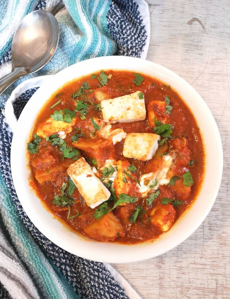 Aloo Paneer served in a white bowl on a white board with blue napkin and a spoon and garnished with finely chopped coriander leaves, aloo paneer recipe