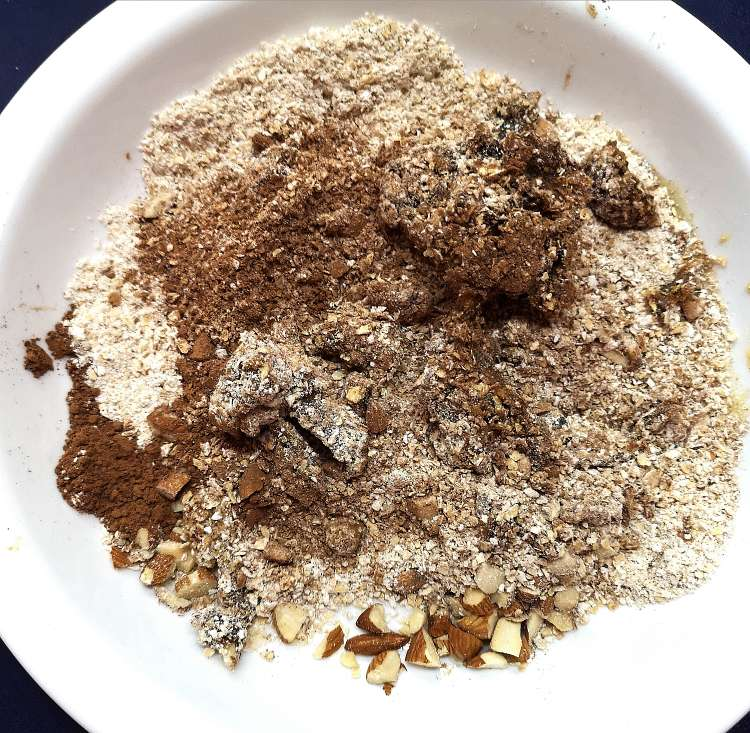 mixing oats, coco powder, honey, almonds, dates for Brownie Energy Bites recipe