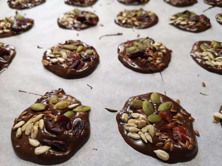 mini detox chocolate bites topped with sunflower seeds, pumpkin seeds, cranberry and flax seeds