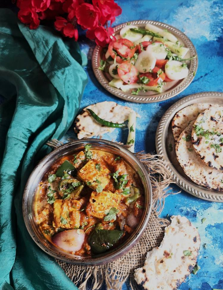 paneer tikka masala recipe | paneer tikka masala served with butter roti and cucumber and onion slices on a blue board with red flowers and satin green cloth