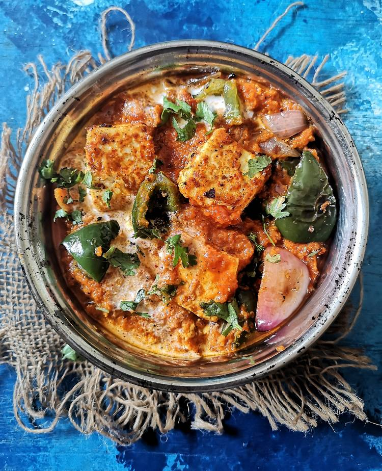 paneer tikka masala served in a round bowl kept underneath a jute cloth on a blue board and garnished with fresh coriander leaves