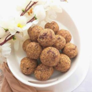 4 Ingredients Peanut Butter Energy Bites served on a white plate and decorated with white flowers