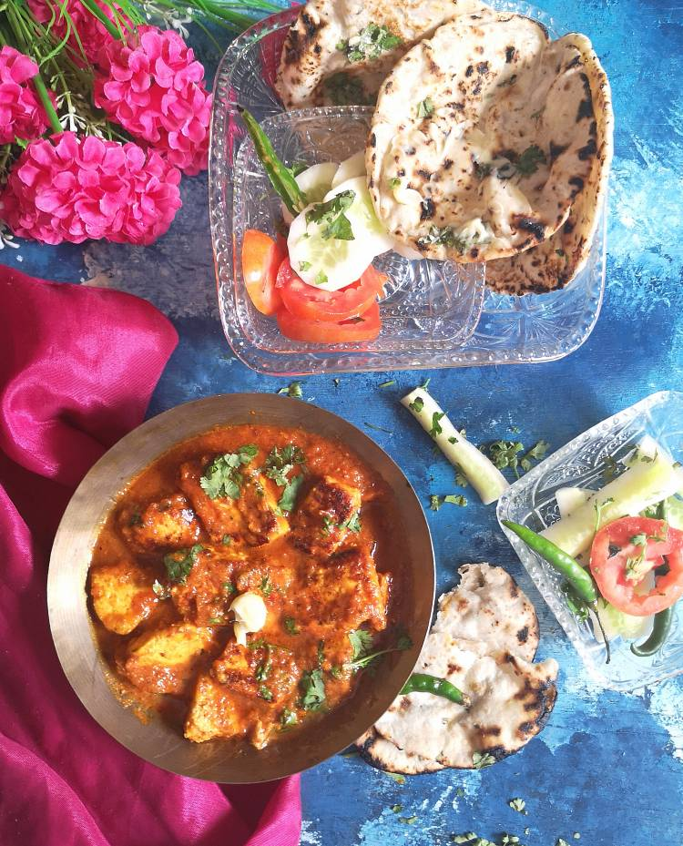 overhead photo of tawa paneer masala with gravy garnished with fresh coriander leaves, fresh cream, served with butter tandoori rotis and cucumber, tomato slices with green chilies, how to make restaurant style tawa paneer masala at home , recipe of tawa paneer masala