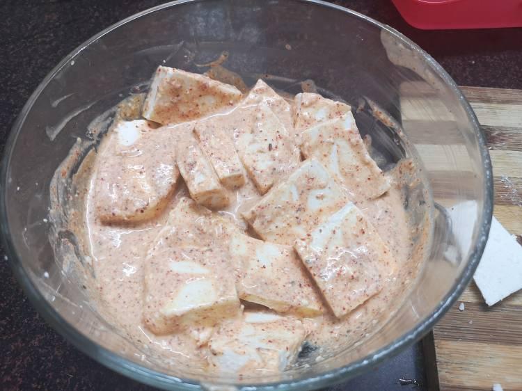 marinating paneer cubes in yogurt with spices like turmeric powder, red chili powder, coriander powder, kasuri methi for tawa paneer masala