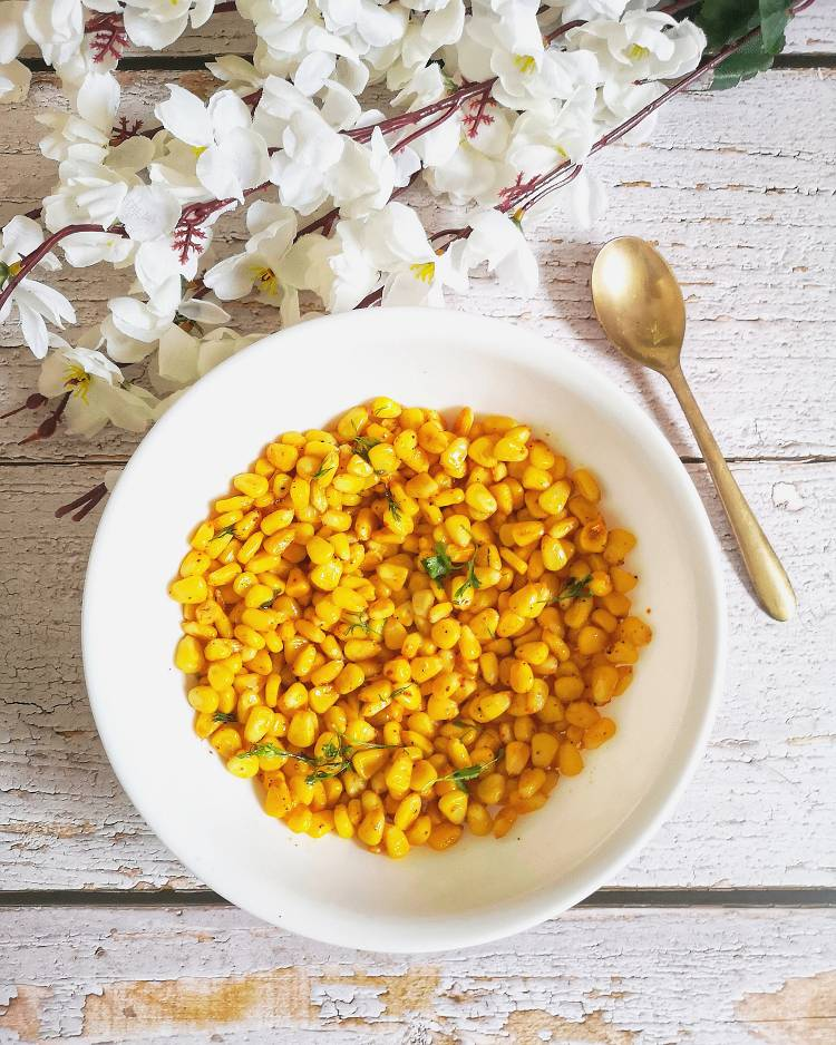 Overhead Photo of buttered corn presented on a wooden white board served in a deep white ceramic bowl with a brass spoon, and dry white flowers