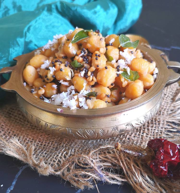 close up view of channa sundal garnished with fresh coconut and curry leaves