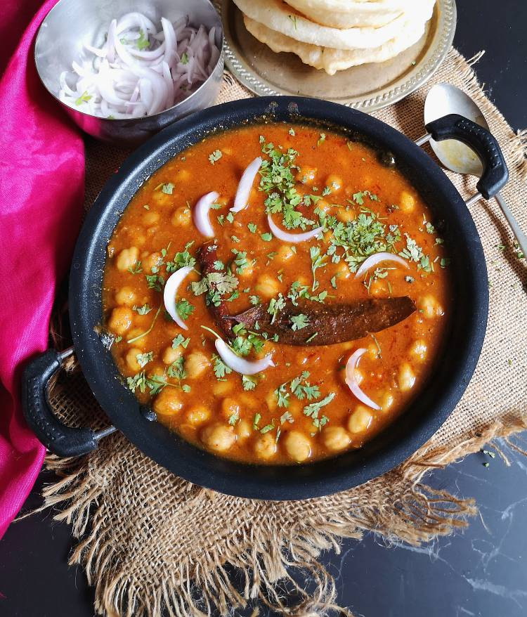 chole bhatue garnished with coriander leaves and sliced onions