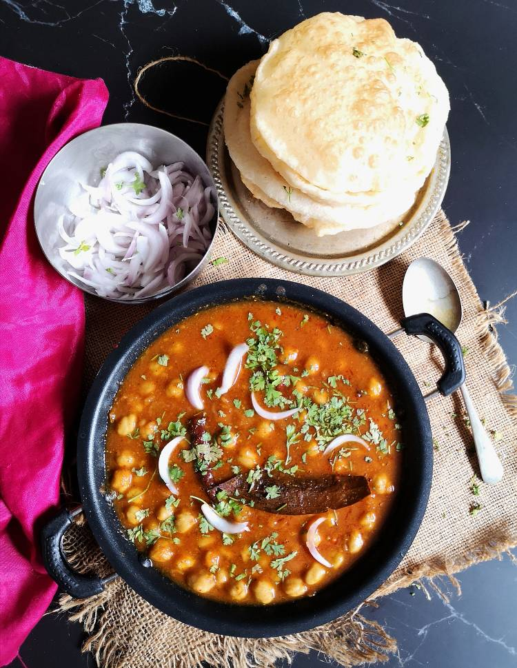 punjabi chole recipe, chole served with bhatura and sliced onions served on a black board and jute cloth
