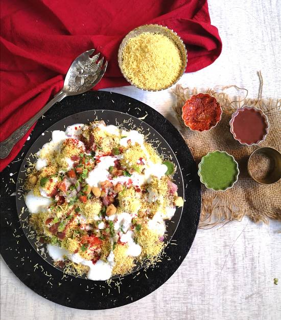 top view image of Dahi bhalla papdi chaat recipe served with garlic chutney, khajur, dates chutney, green coriander chutney, nylon sev with a silver spoon and red cotton napkin.