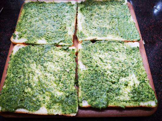 applying butter and coriander chutney on slices of bread for grilled potato sandwich