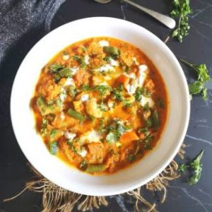 Mix Vegetable Curry served in a white glass bowl garnished with fresh coriander on a black board with grey cloth