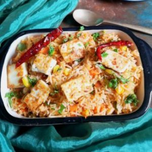 close up photo of Paneer Pulao with marinated paneer cubes, dry red chili, coriander leaves, served with Mushroom Kadai, with a spoon and a green satin cloth, how to make paneer pulao