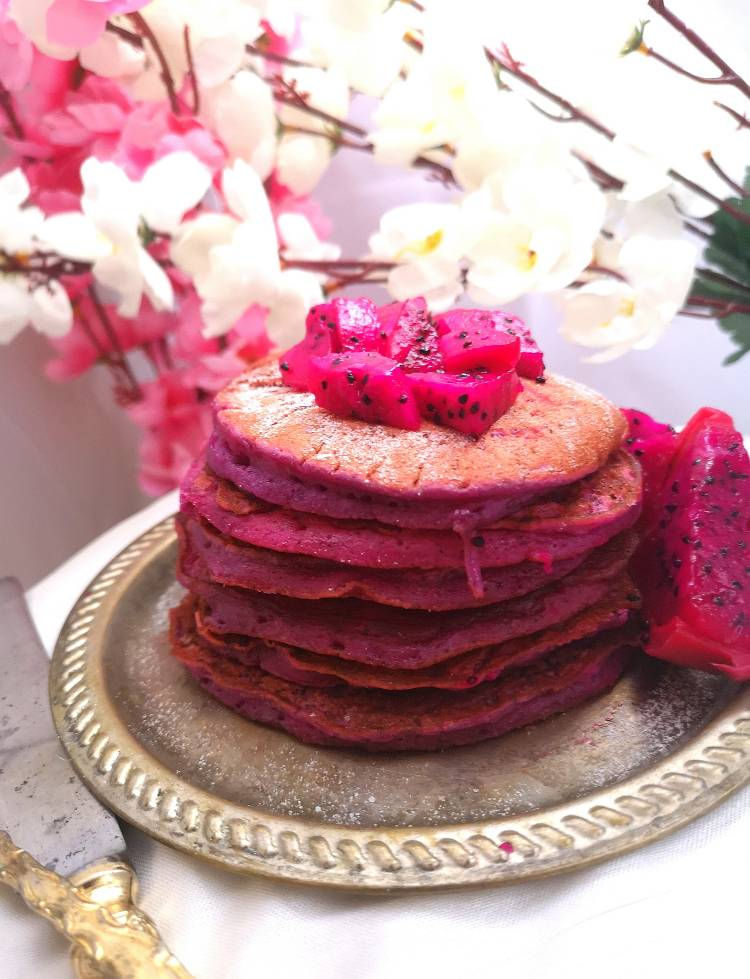 stack of Pink Pitaya Pancakes topped with fresh small chunks of pink dragon fruit and decorated with pink and white flowers