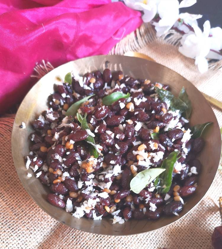 rajma sundal served in a brass bowl and garnished with fresh coconut and curry leaves
