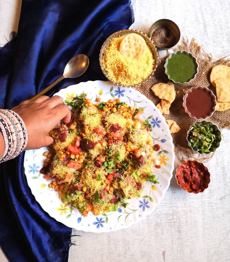 Sev Puri served with dates, coriander and garlic chutney along with papdis and nylon sev
