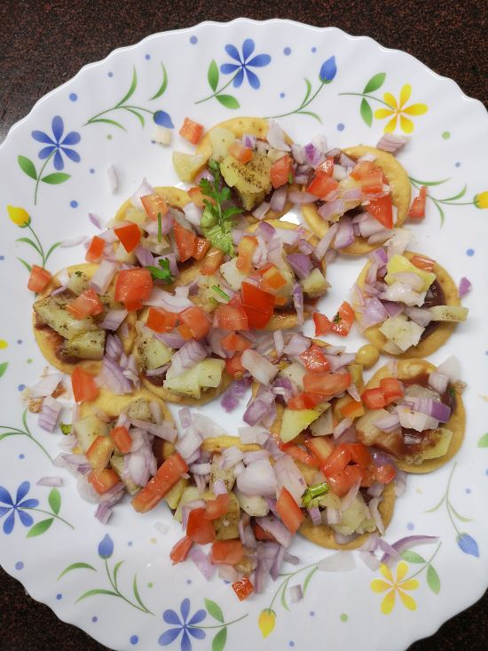 finely chopped tomatoes on sev puri