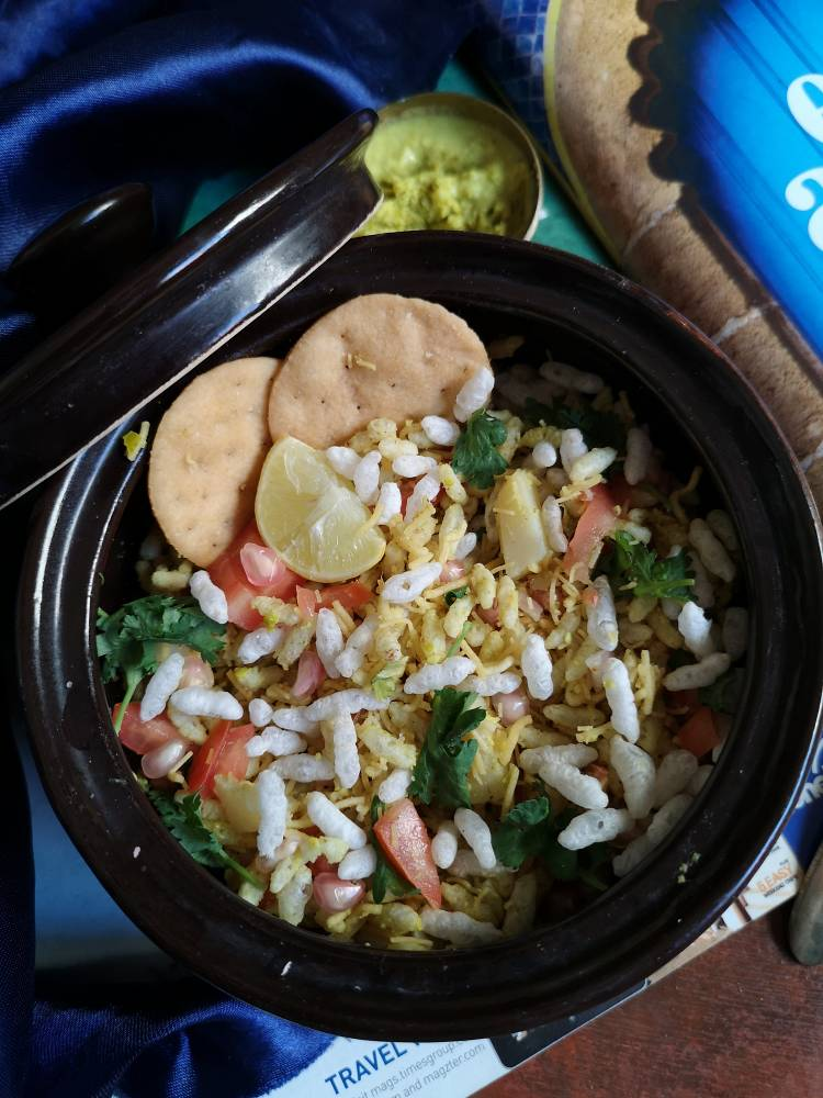 close up view of sukha bhel served with papdis, sev and garnished with coriander leaves, pomegranates and a wedge of lemon