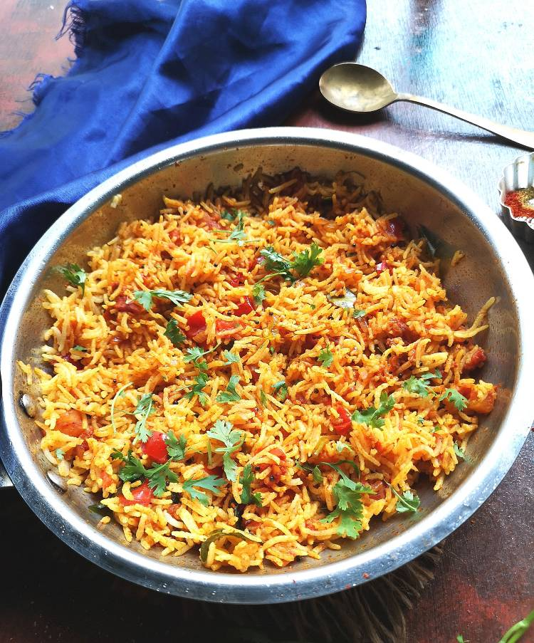 tomato rice served in a steel pan, garnished with finely chopped coriander leaves and