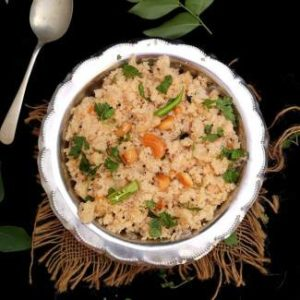Upma Recipe for Breakfast / Upma garnished with coriander leaves, cashew nuts and served in a steel bowl