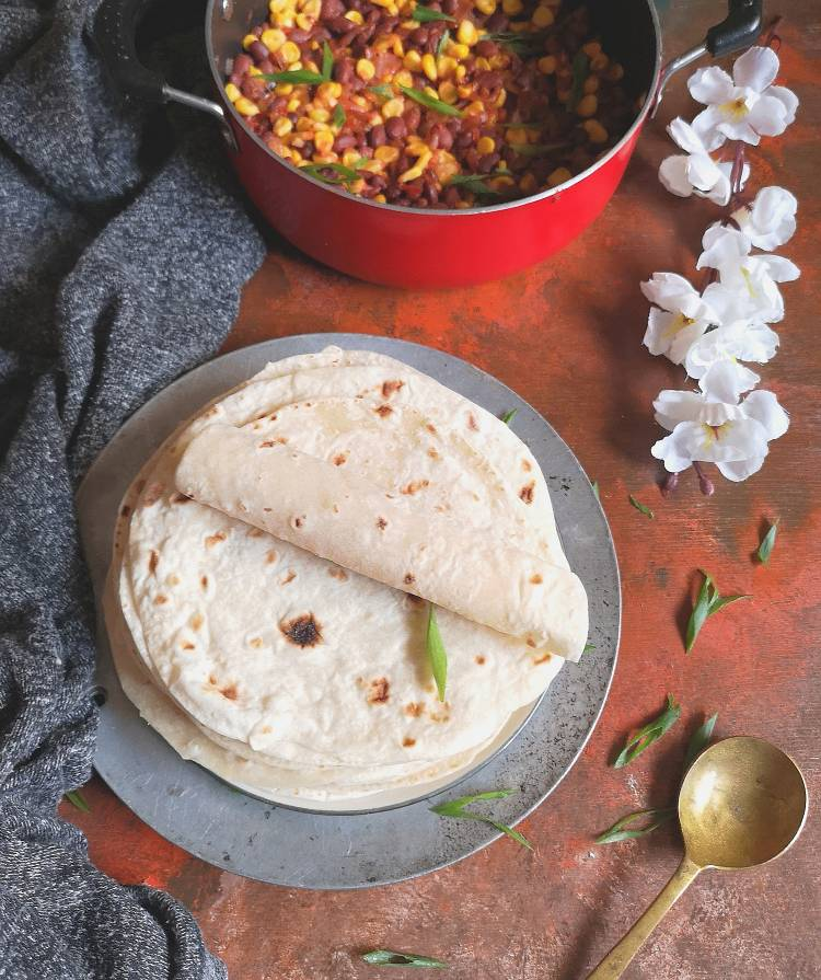 mexican flour tortillas with beans and corn casserole along with a spoon and flower in the background