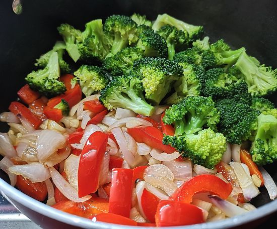 adding steamed broccoli to the pan for making galette recipe