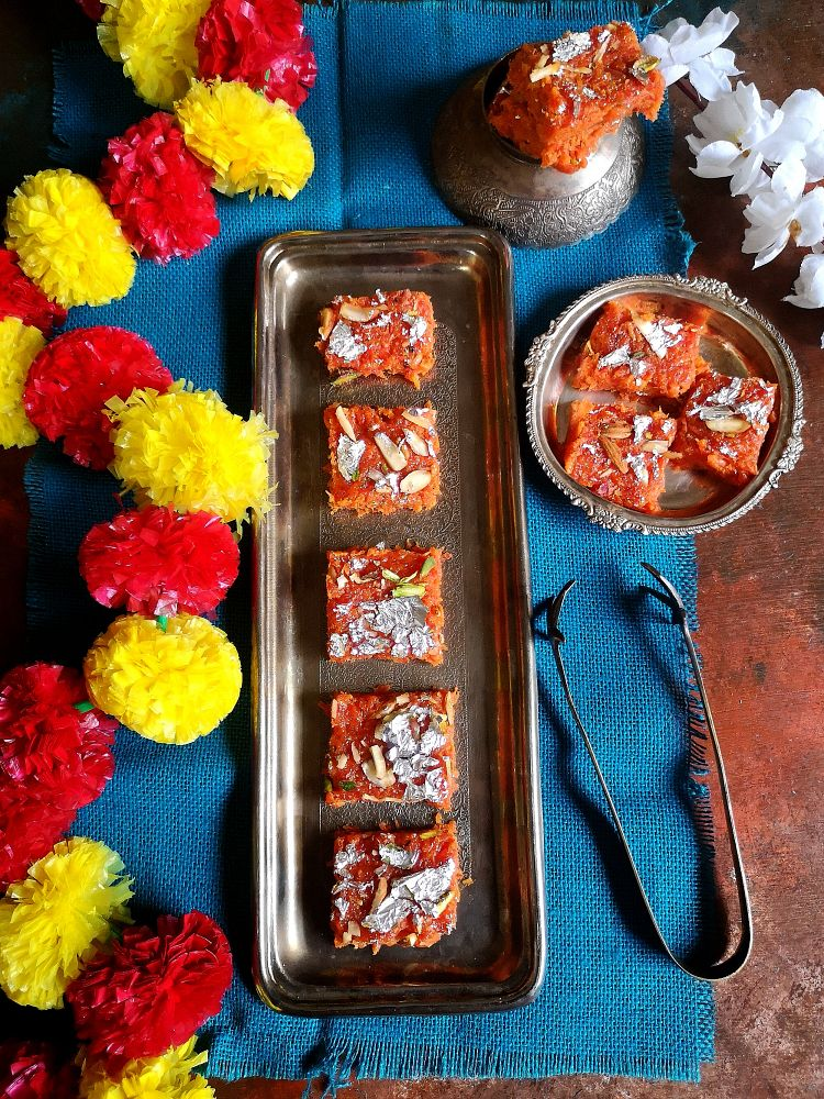 Recipe of Gajar Ki Barfi, How to make Carrot barfi, carrot barfi plated nicely on silver tray with flowers and blue jute cloth