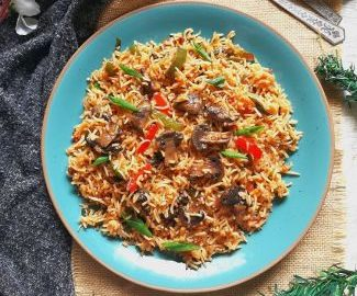 Overhead view of Mushroom Fried Rice garnished with spring onion served with a spoon and a fork with grey fabric at the background