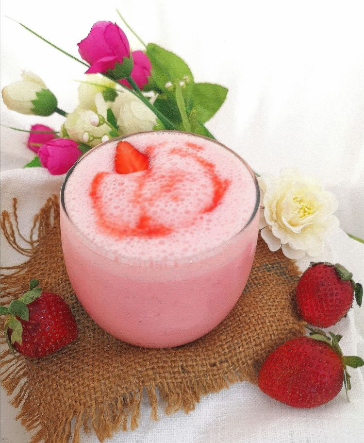 close up view of frothy and creamy Strawberry Yogurt Drink topped with fresh strawberry