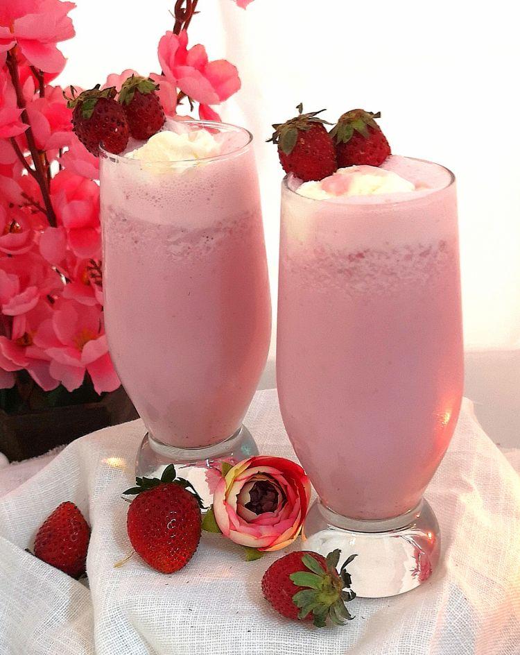 2 chilled glasses of strawberry milkshake garnished with fresh strawberries