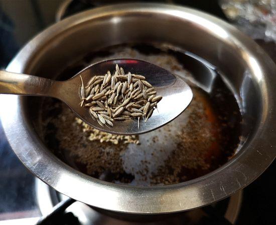adding jeera to tea concoction for hajmola chai
