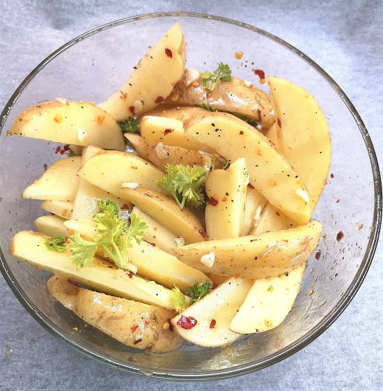 tossing cut potatoes wedges into olive oil and spices seasoning for potato wedges, Recipe of Baked Garlic Potatoes