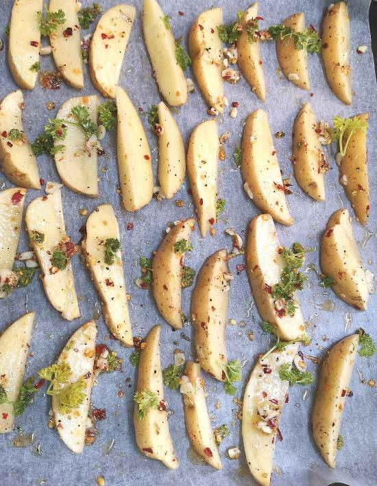 placing all the potato wedges coated with seasoning into the oven tray lined with parchment paper, ready to be baked