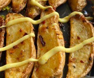 Crispy Garlic Potato Wedges, close up view of Baked Garlic Potato Wedges drizzled with spiced mayonnaise
