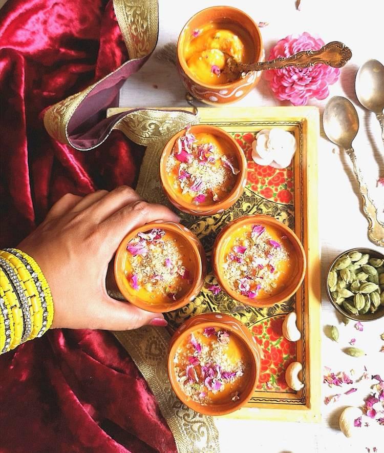 overhread photo of mango matka kulfi, garnished with almonds, pista and dry rose petals, How to Make Mango Matka Kulfi