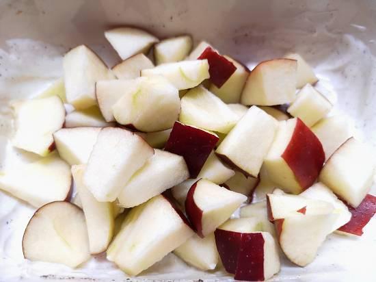 adding apple chunks into the yogurt salad