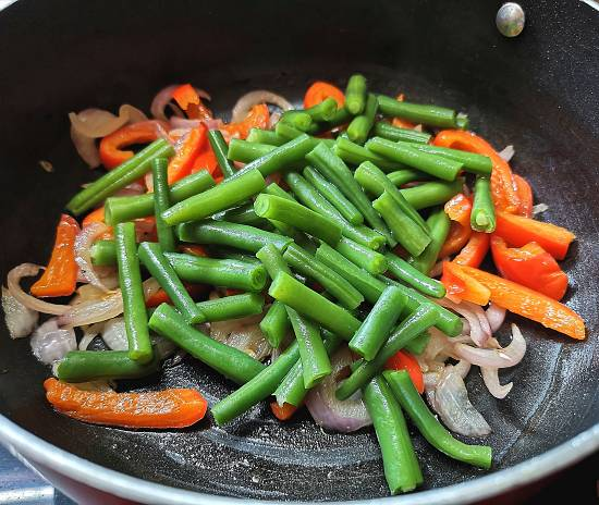 Adding boiled French Beans into the cooked onions and red bell pepper